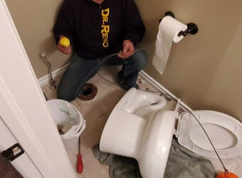 a picture of a toilet and a plumber